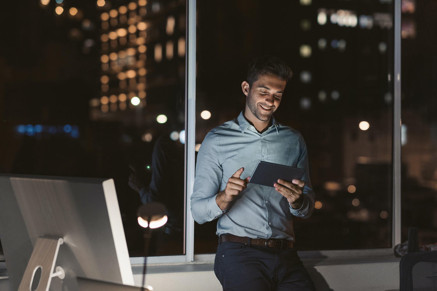 Smiling young businessman standing alone in an office working with a digital tablet late at night with city lights in the background